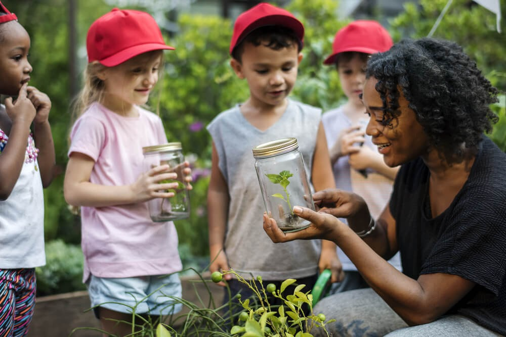 Kids gather around a woman holding a jar and showing them a small plant.
