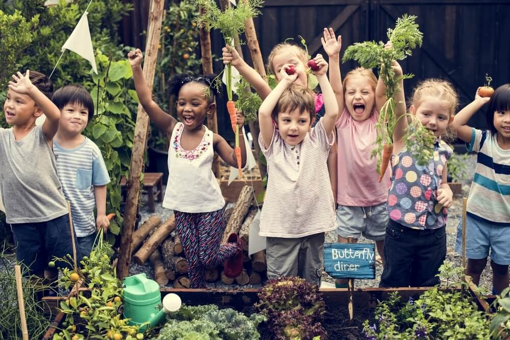 Excited kids hold up plants and vegetables.