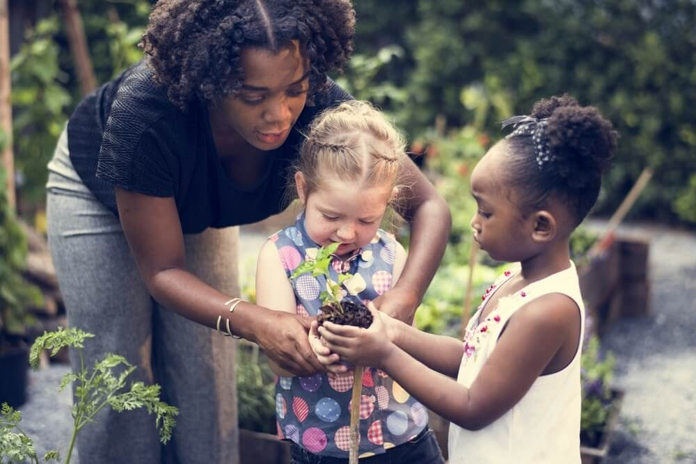 Woman helps two kids with a plant.