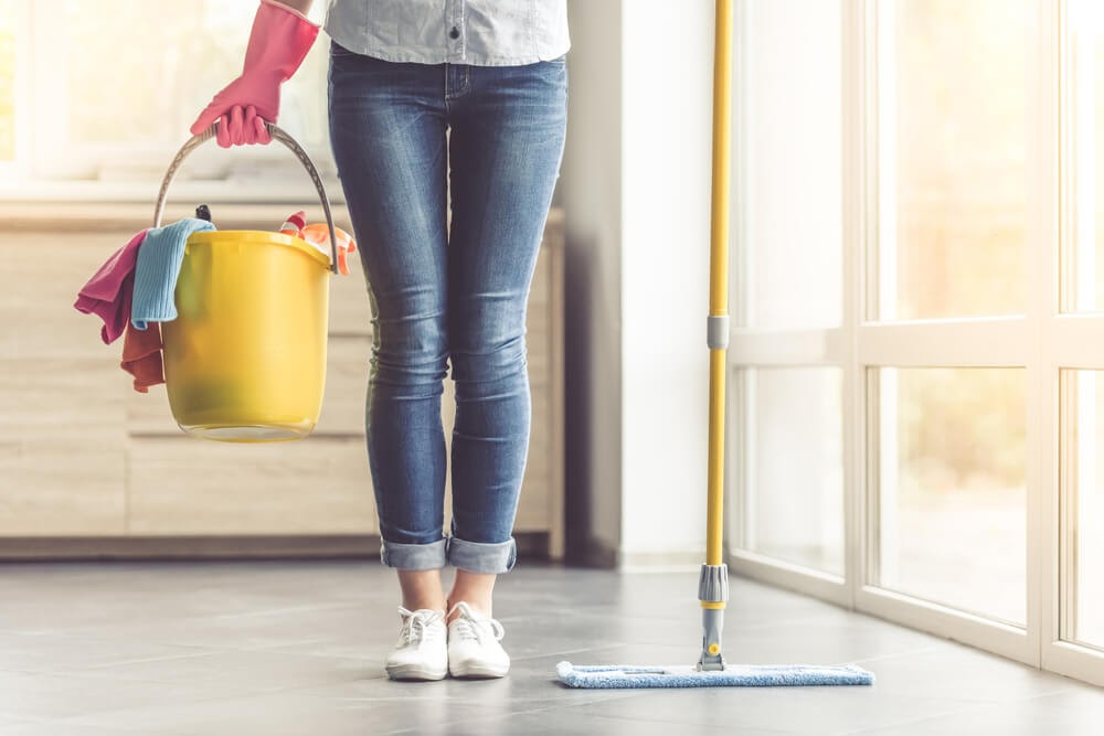 Woman from the waist down holding a mop and a bucket full of cleaning supplies.