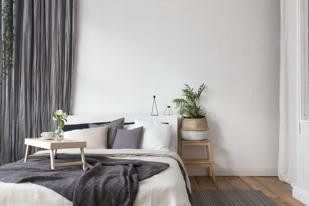 White & grey bedroom with greenery to accent.