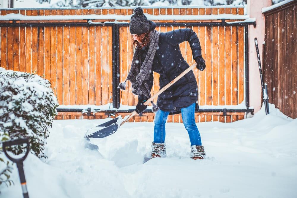 Woman shovels snow during snowfall.