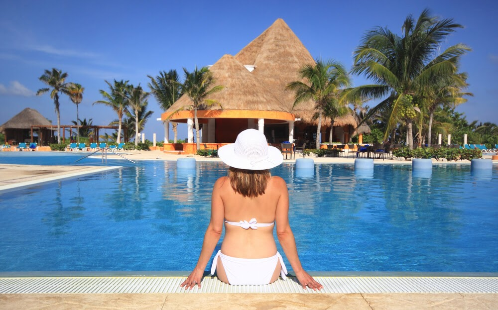 Woman in a white bikini shown sitting poolside from behind.