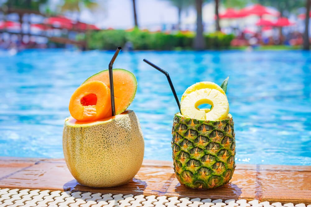 Tropical drinks served poolside in a pineapple and a melon.