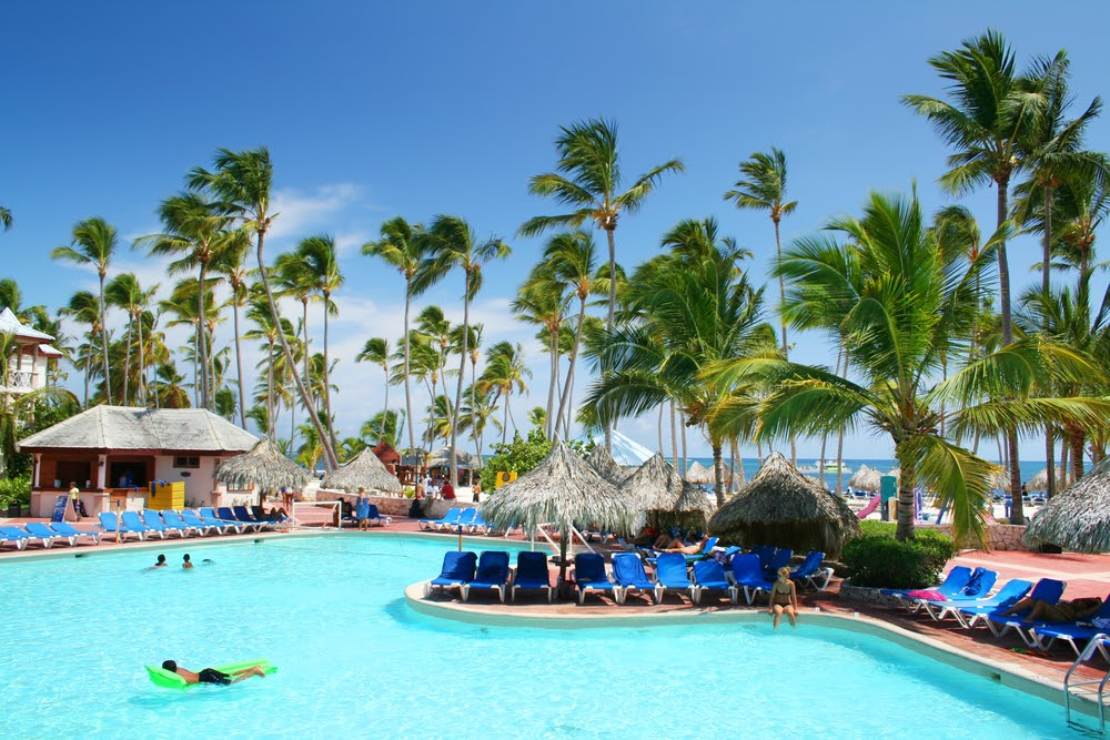 Resort pool with grass cabanas, surrounded by blue lounge chairs.