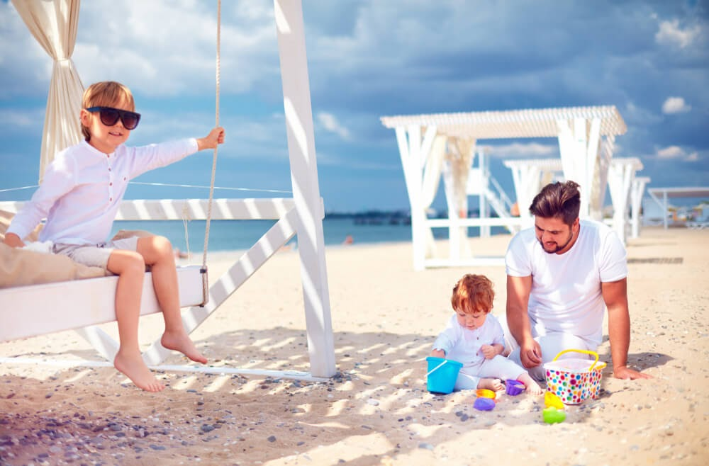 Family all dressed in white play on a white sand beach under a blue sky.