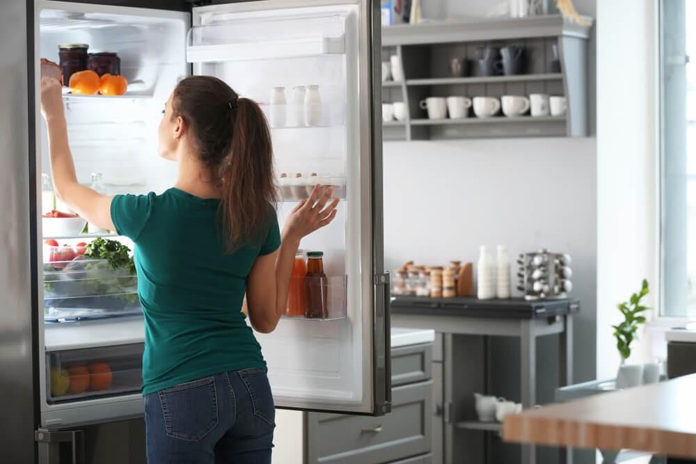 Woman looking into fridge.