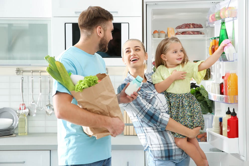 Family putting groceries into the fridge.
