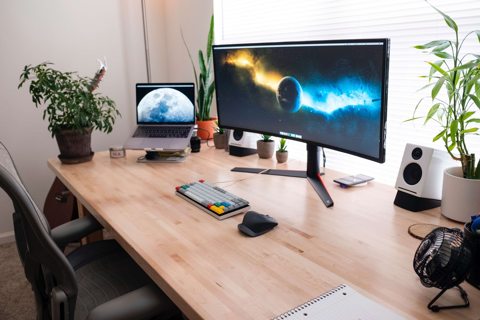 Large monitor with keyboard and laptop. Looks like a home office setup.