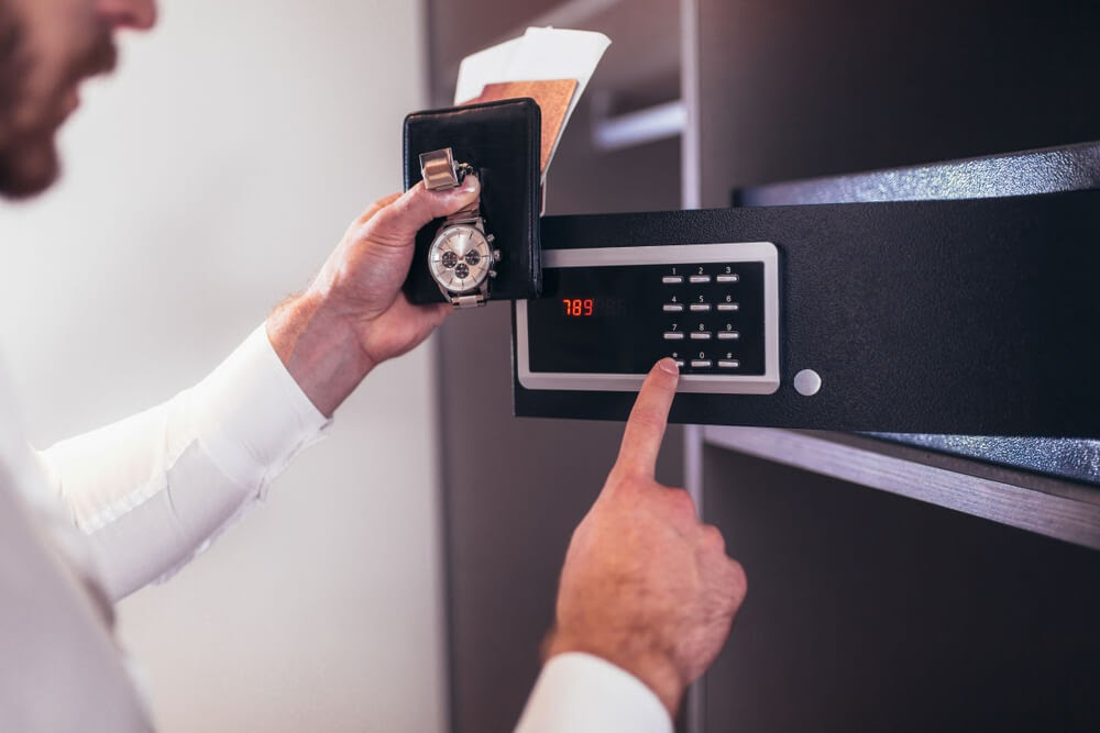 Man putting valuables into a safe.