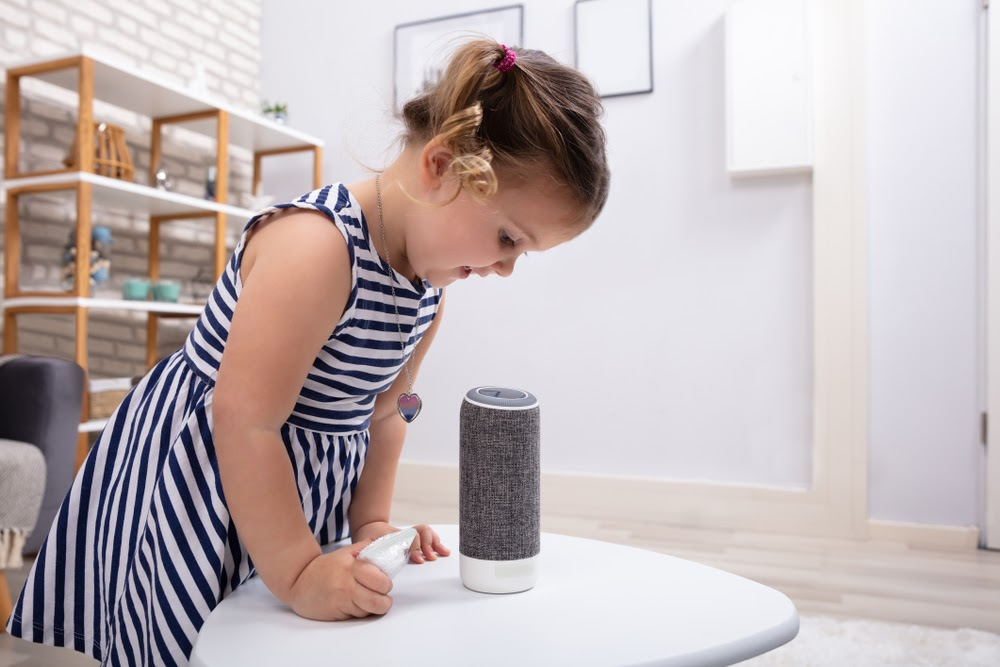 Child playing with bluetooth speaker.