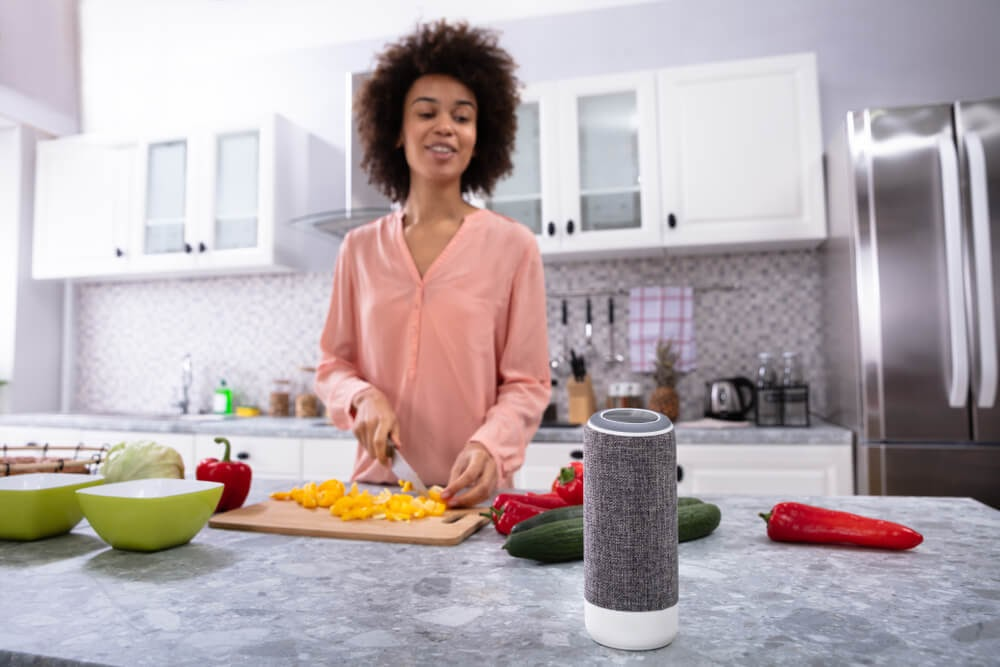 Woman cooking dinner and talking to a smart speaker.
