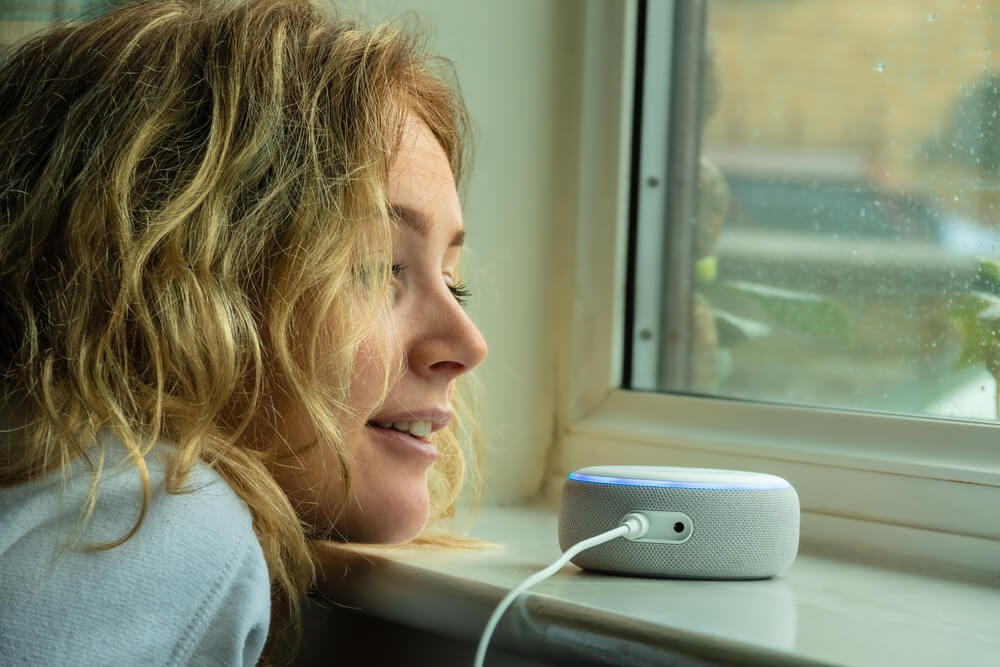 Woman looking out a window with an Alexa speaker near her.