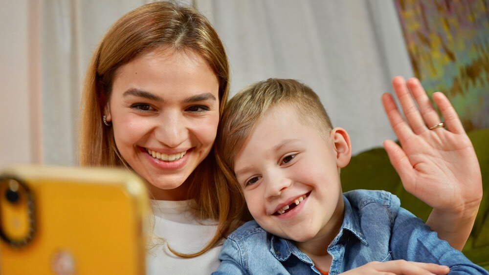 Woman and small child smile at a smartphone.