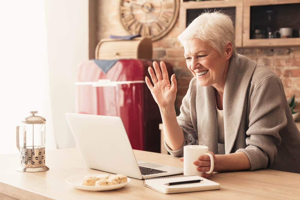 Older woman smiles and waves at laptop.