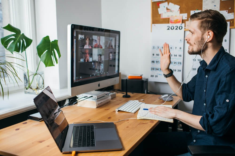 Man speaks to a computer monitor during a virtual meeting.