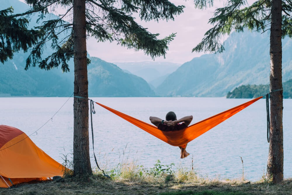 Person lounges in a hammock suspended by two trees and looks out over a lake.
