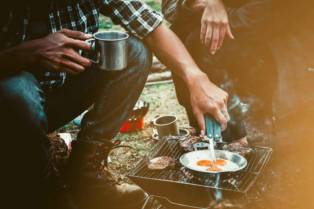 Two people cooking over a camp stove
