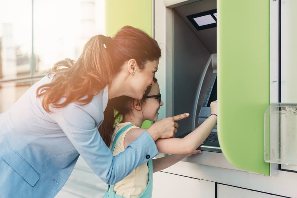 Woman uses ATM with help of young child