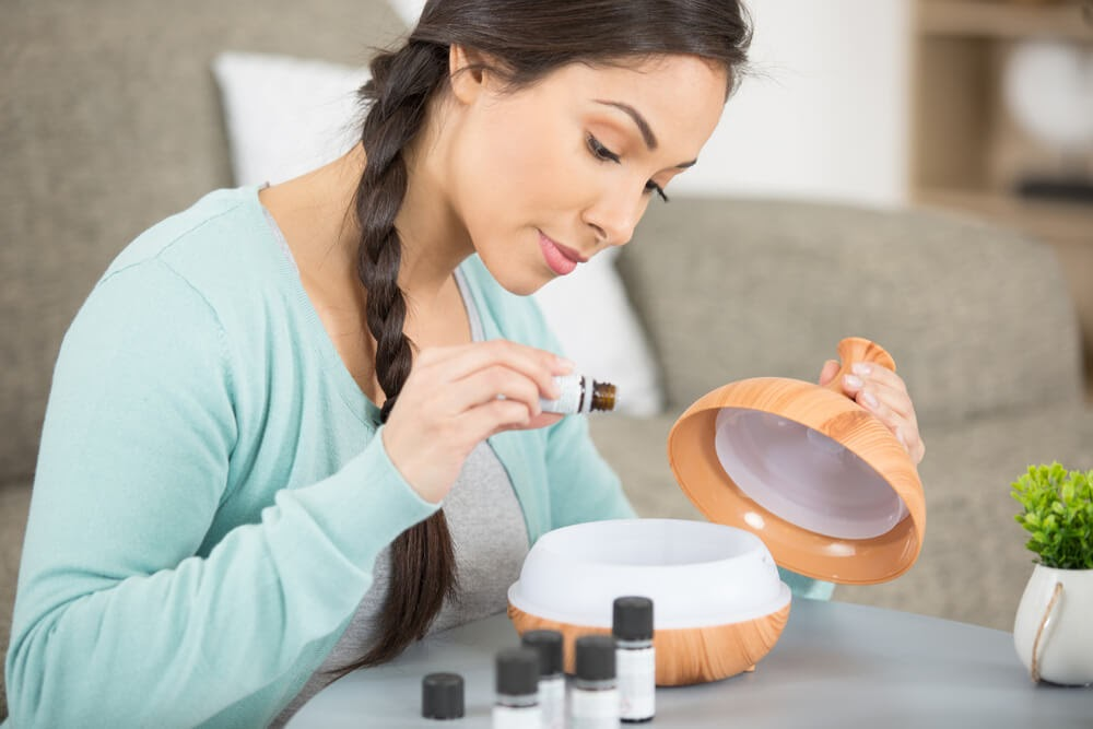 Woman putting oils into a diffuser.