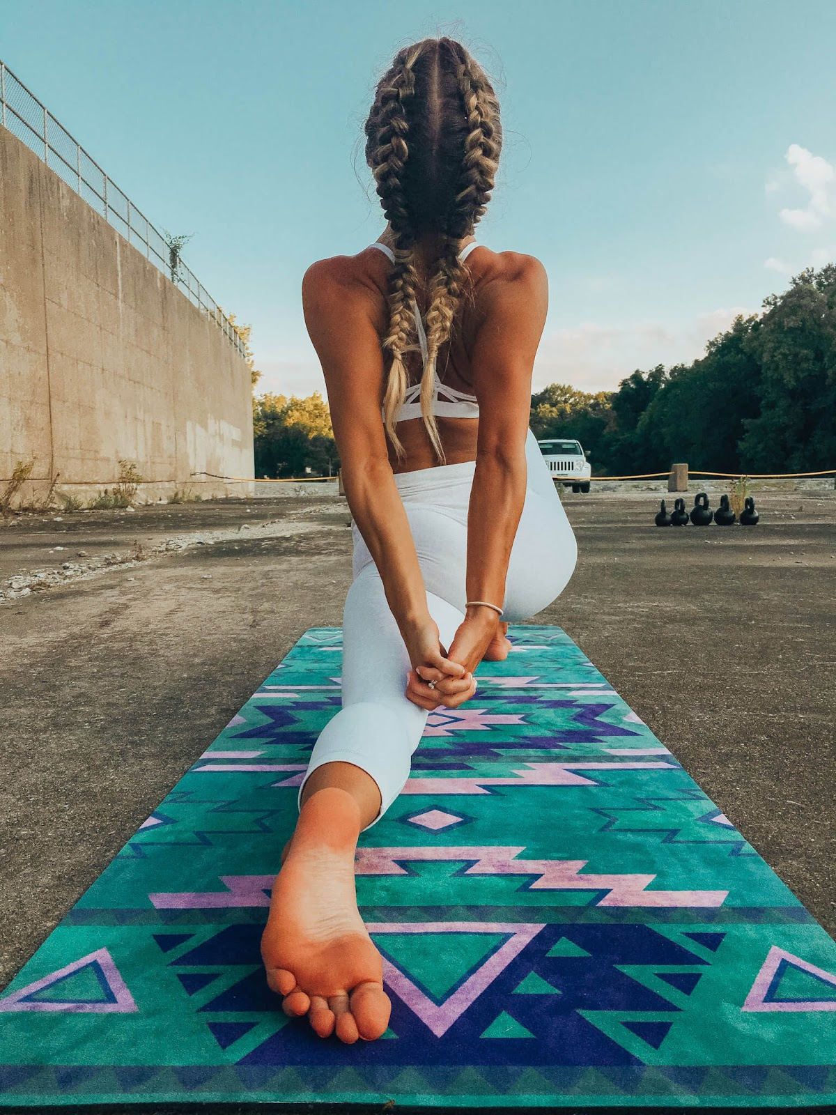 Woman stretching on yoga mat from behind.