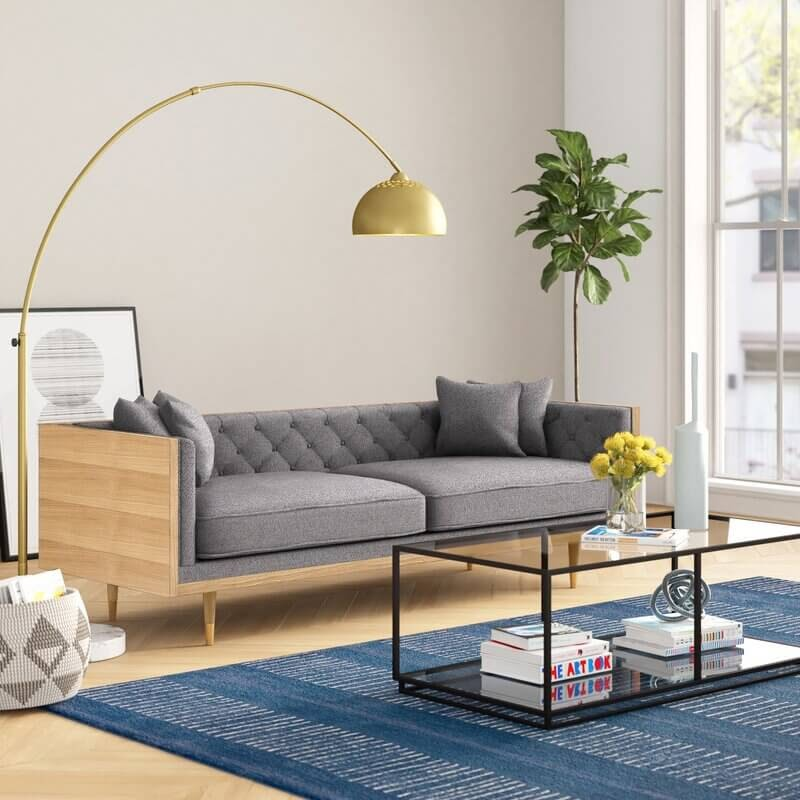 Sun filled living room with grey couch and gold curved lamp.