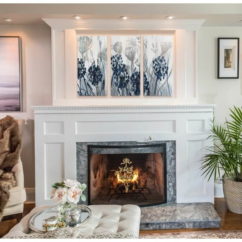 Three piece floral panel hung above a fire place.
