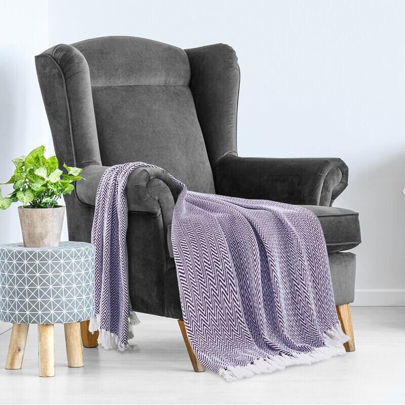 Grey chair with blue throw blanket.