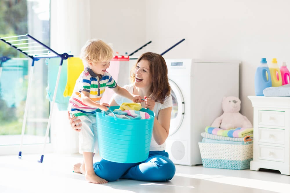 Woman and small child doing laundry in sun-filled room.