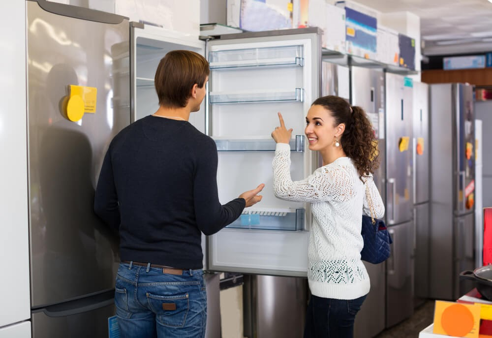Couple shopping for a fridge.