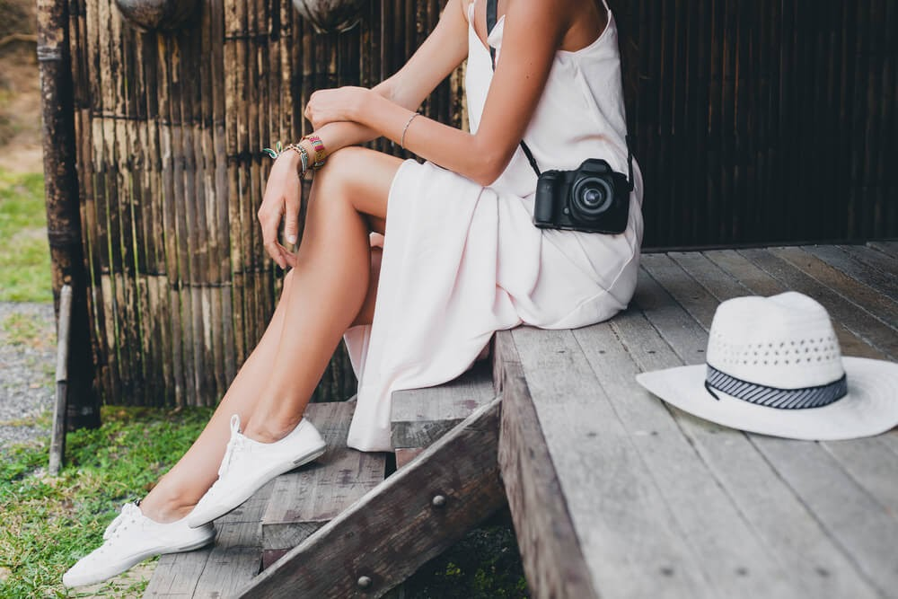 Woman sitting in casual white dress wearing a camera and sneakers.