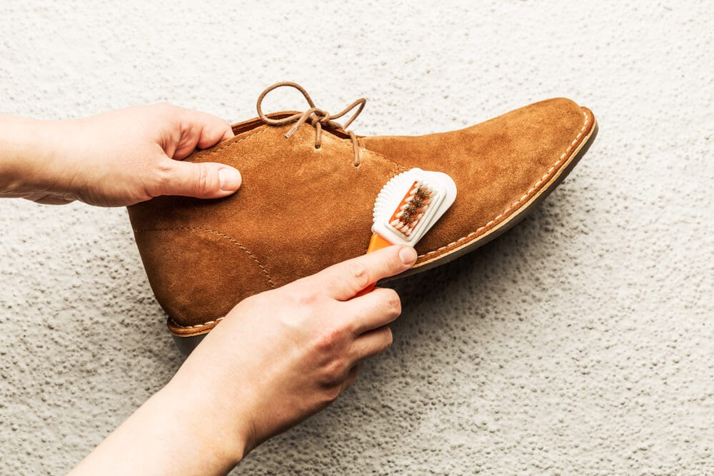 Person cleaning brown suede shoes with a brush.