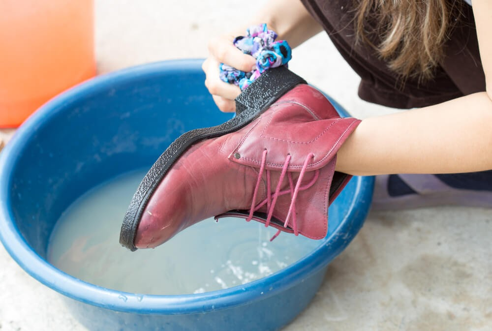 Person scrubbing pink boots in a blue wash basin.