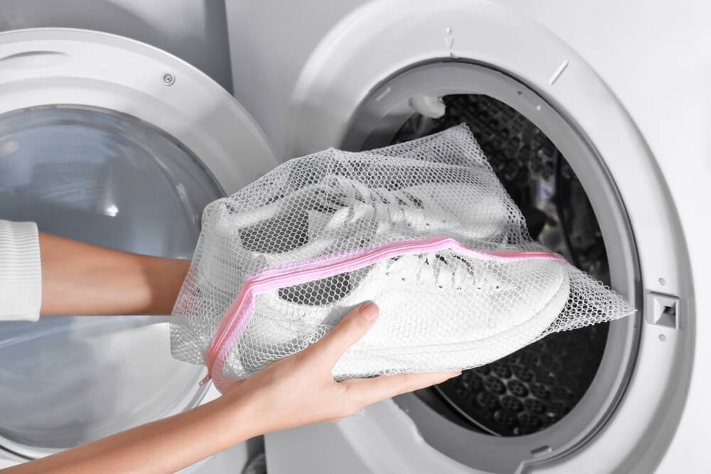 Shoes in delicate washable bag being put in washer.