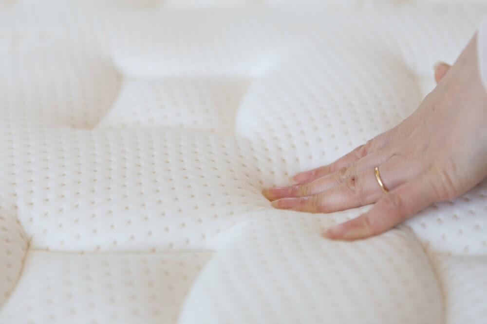 Woman's hand pressing on a mattress
