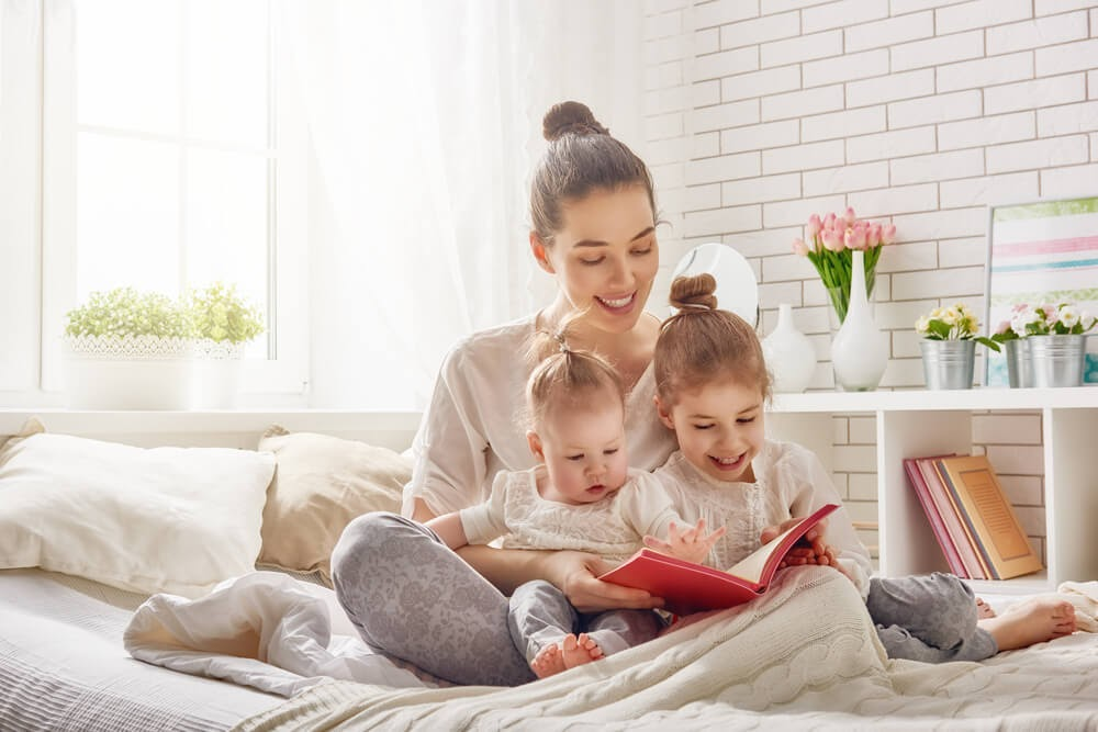 Mom reading to two toddler girls
