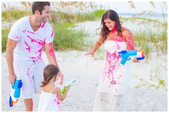 Family squirting pink paint through squirt guns on each other.