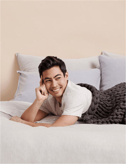 Man wrapped up in weighted blanket on bed