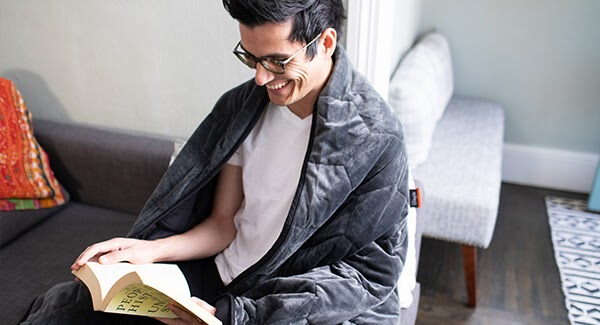 Man reading while wrapped up in blanket