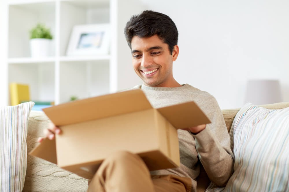 Man opening a box on his couch