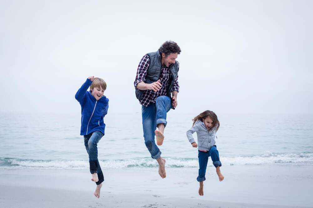 Dad and children frolicking on beach