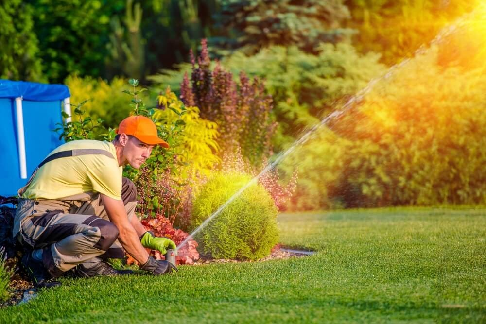 Man adjusting a sprinkler in a lush backyard