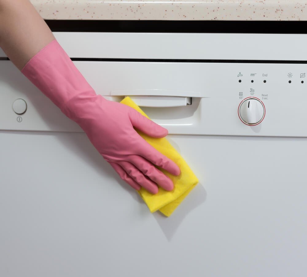 Gloved hand wiping down the front of the dishwasher with a sponge