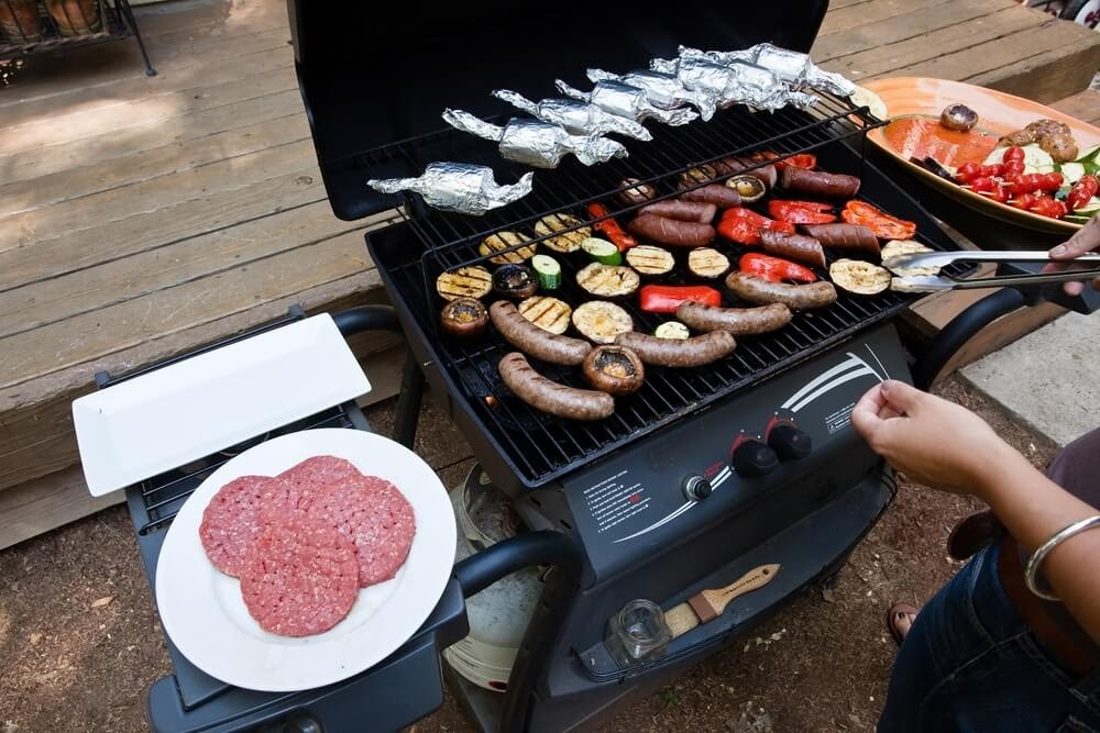 Fully stocked gas grill with meat and veggies