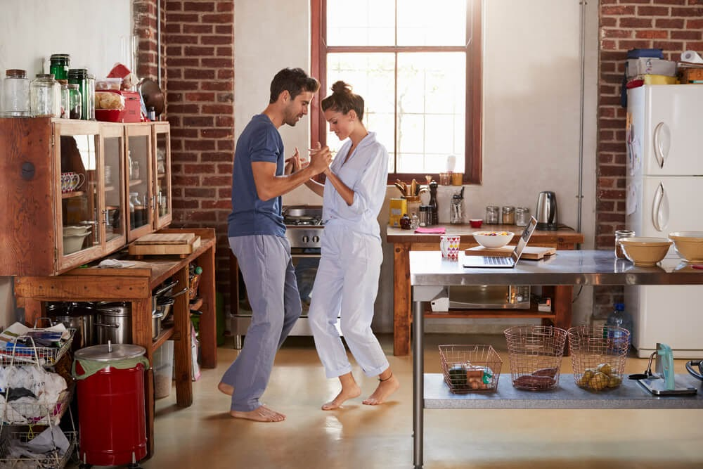 Man  and woman dancing in their  kitchen