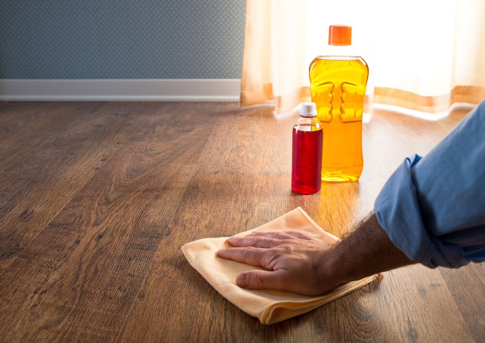 Man wiping down hardwood floor with cleaners  in the background