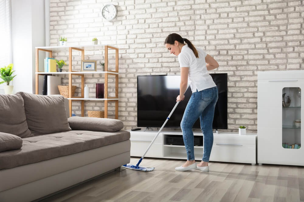 Woman dry mopping hardwood floors with beautiful brick wall in the  background