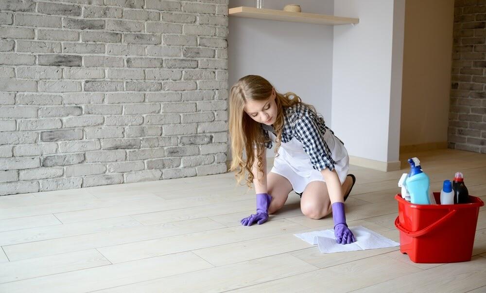 Woman on her hands and knees scrubbing floor