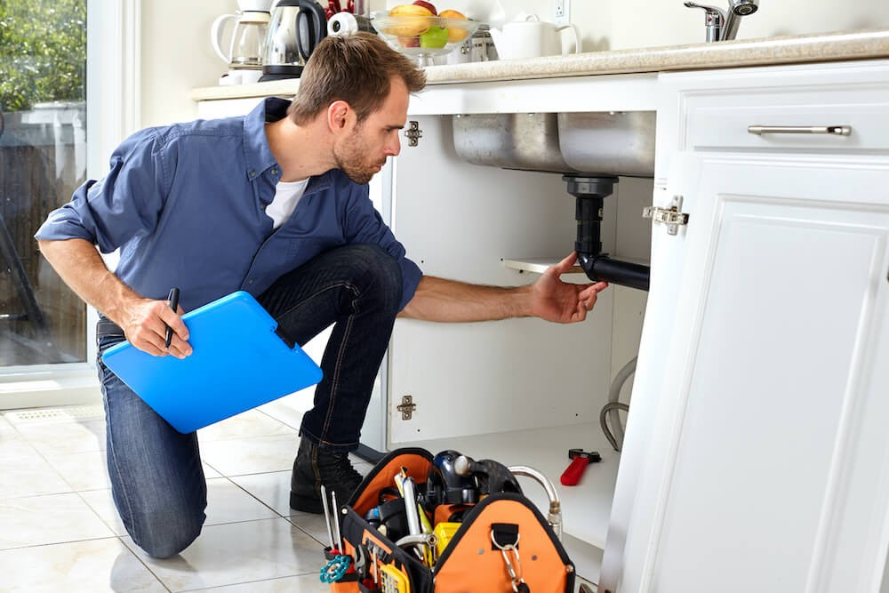 Man looking at the plumbing under the sink.