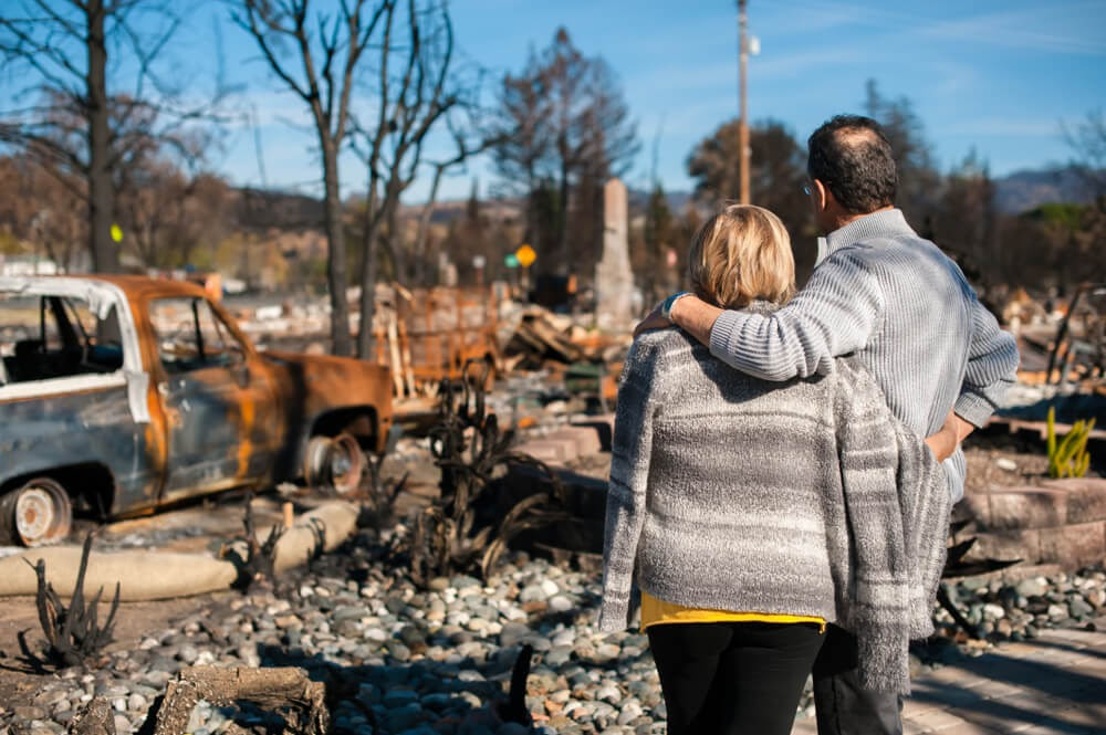 Man and woman looking onto total devastation